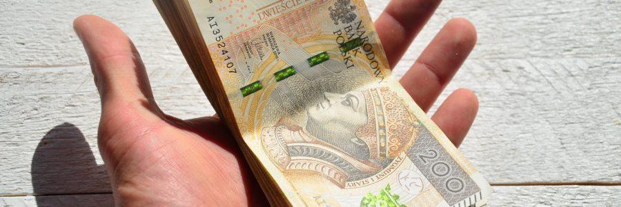 mężczyzna trzyma pieniądze w dłoni